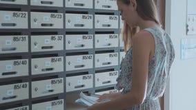Νέα γυναίκα που ελέγχει την ταχυδρομική θυρίδα στο condo, εσωτερικό φιλμ μικρού μήκους