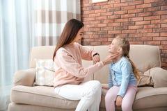 Νέα γυναίκα που ελέγχει το σφυγμό του μικρού κοριτσιού με τα δάχτυλα στοκ εικόνα