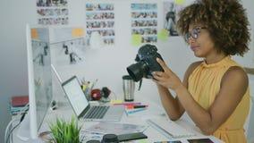 Νέα γυναίκα που εξερευνά τις φωτογραφίες στη κάμερα απόθεμα βίντεο