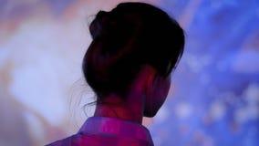 Νέα γυναίκα που εξετάζει γύρω τη σύγχρονη immersive έκθεση φιλμ μικρού μήκους