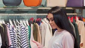 Νέα γυναίκα που εξετάζει τα ενδύματα στην πώληση στο κατάστημα μόδας απόθεμα βίντεο