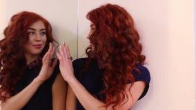 Νέα γυναίκα που εξετάζει την στον καθρέφτη και το γυαλί αφών απόθεμα βίντεο