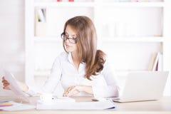 Νέα γυναίκα που εξετάζει τη γραφική εργασία Στοκ Εικόνες