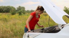 Νέα γυναίκα που εξετάζει τη μηχανή του αυτοκινήτου διακοπής στον τομέα φιλμ μικρού μήκους