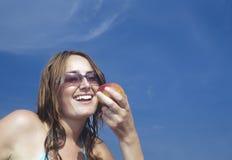 Νέα γυναίκα που εξετάζει τη Apple και το χαμόγελο Στοκ φωτογραφία με δικαίωμα ελεύθερης χρήσης