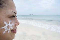 Νέα γυναίκα που εξετάζει τον ήλιο που επισύρεται την προσοχή στο πρόσωπό της Στοκ Εικόνες