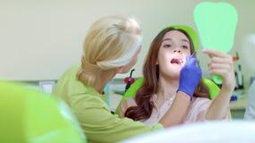 Νέα γυναίκα που εξετάζει τον καθρέφτη στην καρέκλα οδοντιάτρων Θηλυκός οδοντίατρος που θεραπεύει τον ασθενή φιλμ μικρού μήκους