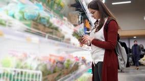Νέα γυναίκα που εξετάζει το μαρούλι και άλλα πράσινα, το οποίο στέκονται σε μια δροσερή θέση απόθεμα βίντεο