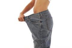 Νέα γυναίκα που επιδεικνύει την απώλεια βάρους στοκ εικόνα