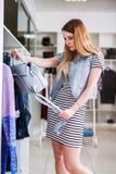 Νέα γυναίκα που επιλέγει τη γυναικεία ένδυση στο κατάστημα ιματισμού Στοκ Εικόνα