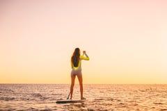 Νέα γυναίκα που επιπλέει στη στάση επάνω στον πίνακα κουπιών με τα θερμά χρώματα ηλιοβασιλέματος στοκ φωτογραφίες