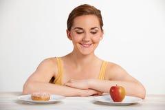 Νέα γυναίκα που επιλέγει μεταξύ Doughnut και του κέικ για το πρόχειρο φαγητό Στοκ φωτογραφία με δικαίωμα ελεύθερης χρήσης