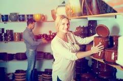 Νέα γυναίκα που επιλέγει τα κεραμικά εμπορεύματα πιάτων στο ατελιέ Στοκ Φωτογραφίες