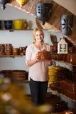 Νέα γυναίκα που επιλέγει τα κεραμικά εμπορεύματα πιάτων στο ατελιέ Στοκ Εικόνες