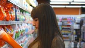 Νέα γυναίκα που επιλέγει τις οικιακές χημικές ουσίες στην υπεραγορά Το όμορφο κορίτσι επιλέγει το αποσκληρυντικό υφάσματος ή τη σ απόθεμα βίντεο