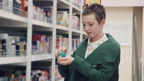 Νέα γυναίκα που επιλέγει το άρωμα στην υπεραγορά απόθεμα βίντεο