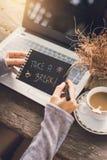 Νέα γυναίκα που εργάζεται με τη χρησιμοποίηση ενός lap-top στον ξύλινο πίνακα Στοκ φωτογραφίες με δικαίωμα ελεύθερης χρήσης