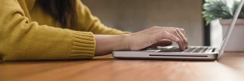 Νέα γυναίκα που εργάζεται με το lap-top σε ένα γραφείο στη καφετερία Νέα γυναίκα που εργάζεται στο Σαββατοκύριακο με το lap-top τ Στοκ φωτογραφίες με δικαίωμα ελεύθερης χρήσης