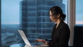 Νέα γυναίκα που εργάζεται στη συνεδρίαση lap-top από το παράθυρο στο γραφείο απόθεμα βίντεο