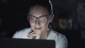 Νέα γυναίκα που εργάζεται στον υπολογιστή στο σκοτάδι Αντανάκλαση του οργάνου ελέγχου με τα γυαλιά φιλμ μικρού μήκους
