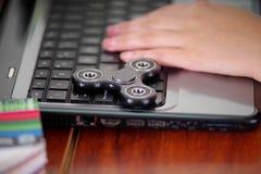 Νέα γυναίκα που εργάζεται στον υπολογιστή και ένα δημοφιλές fidget παιχνίδι κλωστών πέρα από το lap-top, στο υπόβαθρο γραφείων Στοκ Εικόνες