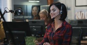 Νέα γυναίκα που εργάζεται στο γραφείο της απόθεμα βίντεο