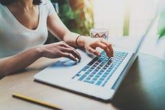 Νέα γυναίκα που εργάζεται στο σπίτι στο σύγχρονο υπολογιστή Δακτυλογράφηση κοριτσιών στο πληκτρολόγιο lap-top καθμένος στον ξύλιν Στοκ φωτογραφία με δικαίωμα ελεύθερης χρήσης