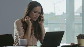 Νέα γυναίκα που εργάζεται στο lap-top Πορτρέτο της χαμογελώντας κυρίας που κουβεντιάζει το κινητό τηλέφωνο απόθεμα βίντεο
