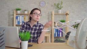 Νέα γυναίκα που εργάζεται στο lap-top στη συνεδρίαση γραφείων μπροστά από τον ανεμιστήρα φιλμ μικρού μήκους