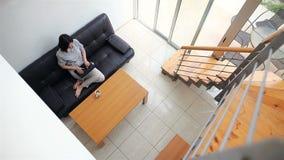 Νέα γυναίκα που εργάζεται στο lap-top στο άνετο σπίτι απόθεμα βίντεο