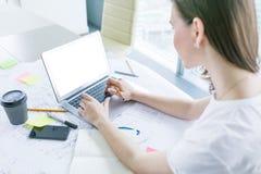 Νέα γυναίκα που εργάζεται στο lap-top στο γραφείο Στοκ Φωτογραφία