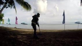 Νέα γυναίκα που εργάζεται ως καθαριστής παραλιών που μαζεύει με τη τσουγκράνα τα απορρίματα, συντρίμμια στην τροπική αμμώδη παραλ φιλμ μικρού μήκους