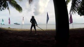 Νέα γυναίκα που εργάζεται ως καθαριστής παραλιών που μαζεύει με τη τσουγκράνα τα απορρίματα, συντρίμμια στην τροπική αμμώδη παραλ απόθεμα βίντεο