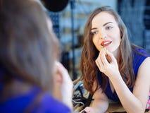 Νέα γυναίκα που εφαρμόζει το κραγιόν μπροστά από έναν καθρέφτη Στοκ Εικόνες