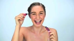 Νέα γυναίκα που εφαρμόζει mascara στο eyelash της φιλμ μικρού μήκους