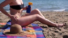 Νέα γυναίκα που εφαρμόζει sunscreen στο δέρμα στην παραλία απόθεμα βίντεο