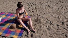 Νέα γυναίκα που εφαρμόζει sunscreen στο δέρμα στην παραλία φιλμ μικρού μήκους