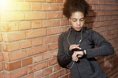 Νέα γυναίκα που ελέγχει τον ιχνηλάτη δραστηριότητας Στοκ Εικόνες