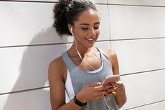 Νέα γυναίκα που ελέγχει app στο κινητό τηλέφωνο Στοκ φωτογραφία με δικαίωμα ελεύθερης χρήσης
