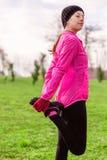 Νέα γυναίκα που θερμαίνει και που τεντώνει τα πόδια πρίν τρέχει σε έναν κρύο χειμώνα, φθινόπωρο της ημέρας πτώσης σε ένα αστικό π στοκ φωτογραφία