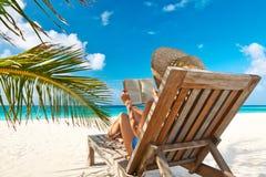 Νέα γυναίκα που διαβάζει ένα βιβλίο στην παραλία στοκ φωτογραφίες