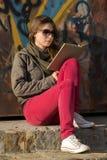 Νέα γυναίκα που διαβάζει ένα βιβλίο Στοκ Εικόνα