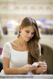 Νέα γυναίκα που διαβάζει ένα μήνυμα στο τηλέφωνο στοκ εικόνες με δικαίωμα ελεύθερης χρήσης