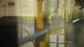 Νέα γυναίκα που διαβάζει μια ταμπλέτα ή ebook σε έναν σταθμό τρένου ενώ περιμένει τις δημόσιες συγκοινωνίες, μέσω της κάμερας λεω απόθεμα βίντεο