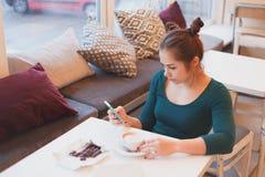 Νέα γυναίκα που διαβάζει τις παγκόσμιες ειδήσεις πρωινού στην έξυπνη τηλεφωνική συνεδρίαση στον καφέ Στοκ Φωτογραφίες