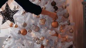 Νέα γυναίκα που διακοσμεί το χριστουγεννιάτικο δέντρο Η νέα προετοιμασία έτους, κλείνει επάνω φιλμ μικρού μήκους