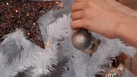 Νέα γυναίκα που διακοσμεί το χριστουγεννιάτικο δέντρο με τα μπιχλιμπίδια Η νέα προετοιμασία έτους, κλείνει επάνω απόθεμα βίντεο