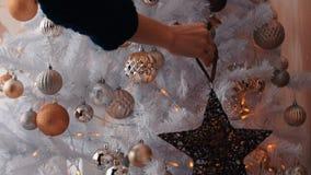 Νέα γυναίκα που διακοσμεί το χριστουγεννιάτικο δέντρο με το αστέρι Η νέα προετοιμασία έτους, κλείνει επάνω φιλμ μικρού μήκους