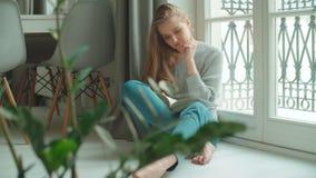 Νέα γυναίκα που κάθεται στο σπίτι κοντά σε ένα βιβλίο και μια χαλάρωση ανάγνωσης παραθύρων απόθεμα βίντεο