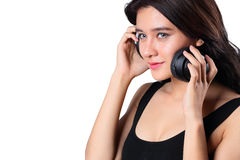 Νέα γυναίκα που κάνει ένα bWoman άκουσμα στη μουσική στα ακουστικά που απολαμβάνουν μια μπούκλα musicicep που απομονώνεται στο μό Στοκ εικόνες με δικαίωμα ελεύθερης χρήσης